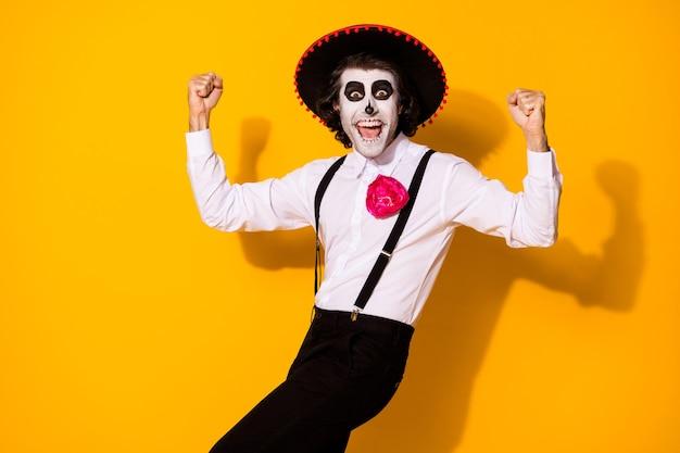 Foto retrato de alegre louco simpático bonito engraçado mexicano em traje tradicional levantando os punhos isolado fundo de cor brilhante amarelo