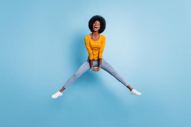 Foto retrato de corpo inteiro de garota energética pulando com as mãos para baixo juntas, isoladas em um fundo de cor azul pastel