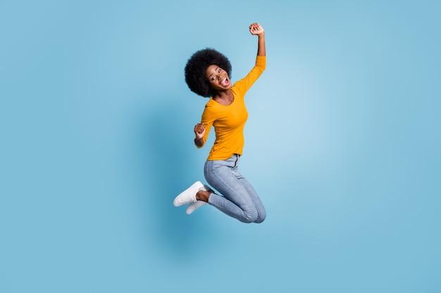 Foto retrato de corpo inteiro de menina alegre pulando comemorando a vitória isolada em um fundo de cor azul pastel