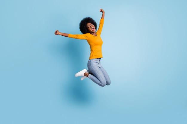 Foto retrato de corpo inteiro de uma garota animada comemorando um salto isolado em um fundo de cor azul pastel