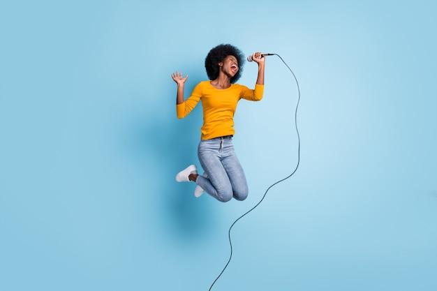 Foto retrato de corpo inteiro de uma mulher cantando segurando o microfone em uma mão, pulando isolado em um fundo de cor azul pastel