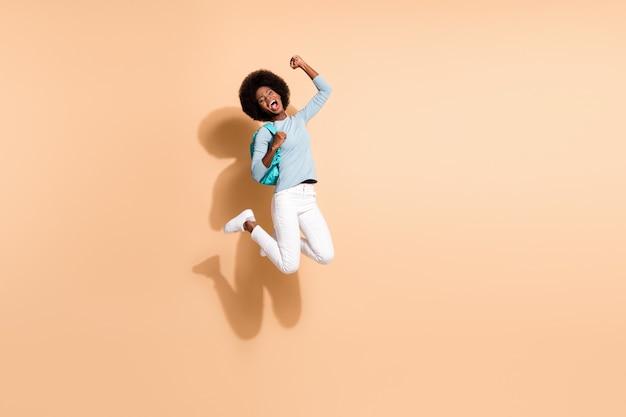 Foto retrato de uma jovem alegre afro-americana, pulando, comemorando a vitória, isolada em um fundo de cor bege pastel