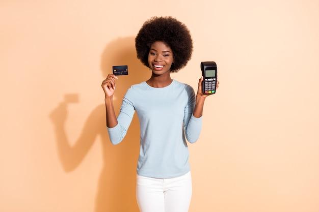 Foto retrato de uma menina morena de pele escura mostrando o cartão de crédito do terminal do banco sorrindo, vestindo uma camisa azul isolada em um fundo de cor bege