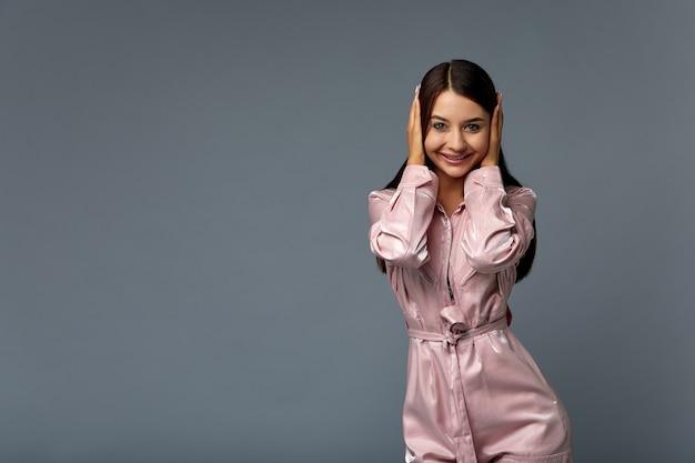 Foto retrato de uma menina mulher bonita com cabelos escuros na roupa rosa com as mãos cobrindo os ouvidos.