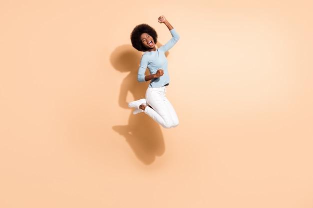 Foto retrato de uma mulher afro-americana morena pulando, comemorando, isolada em um fundo de cor bege pastel