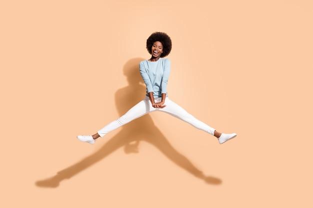 Foto retrato de uma mulher afro-americana pulando de mãos dadas com as pernas abertas e boca aberta isolada em um fundo de cor bege pastel