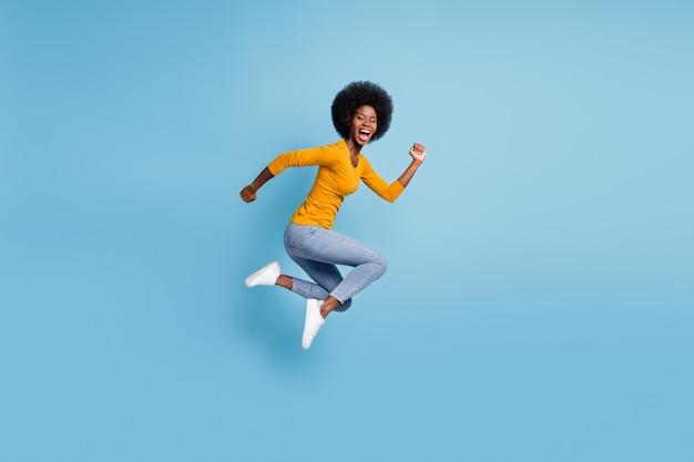Foto retrato em tamanho real de mulher correndo pulando isolada em um fundo de cor azul pastel