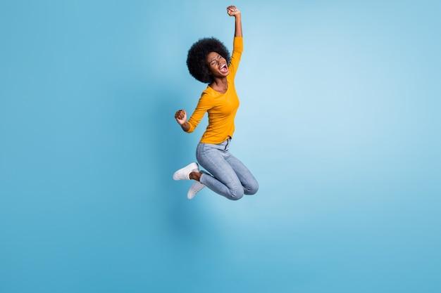 Foto retrato em tamanho real de uma menina morena ativa pulando comemorando isolado em um fundo de cor azul pastel