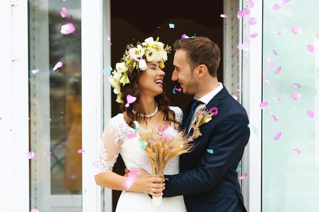 Foto romântica da noiva e do noivo fora, abraçando e sorrindo