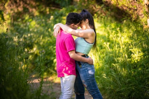 Foto romântica de um casal se abraçando intimamente no meio de uma floresta
