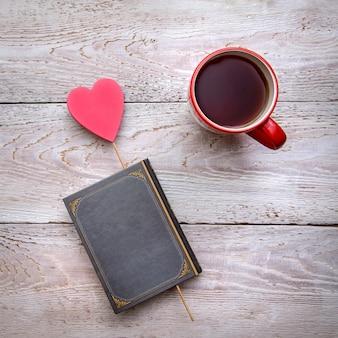 Foto romântica quadrada com uma caneca de chá e um livro com um coração em um fundo rústico de madeira, para o dia dos namorados