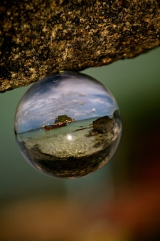 Foto seletiva da praia em koh lipe refletida em uma bola de vidro