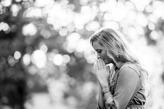Foto seletiva em tons de cinza de uma loira rezando