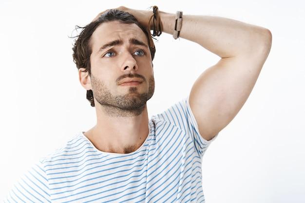 Foto sem retomada de um cara bonito e dramático chateado com barba e homens penteando o cabelo para trás com a mão, fazendo um olhar triste à distância, como se estivesse atuando em um filme dramático, sentindo-se preocupado e triste