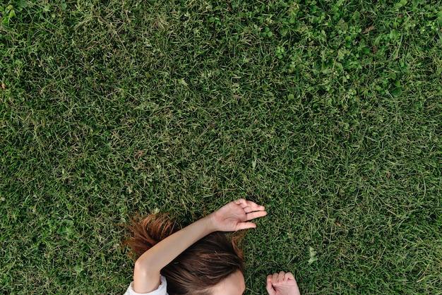 Foto sem rosto de mulher deitada na grama verde