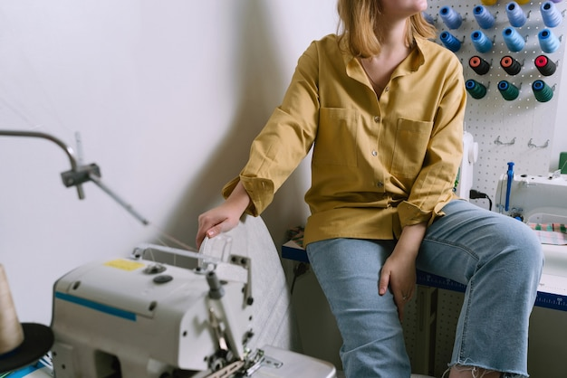 Foto sem rosto de uma jovem mulher de camisa amarela sentada em sua oficina de costura em frente aos fios coloridos