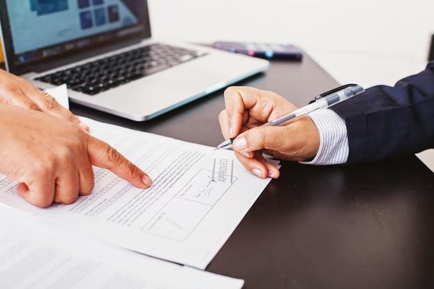 Foto sem rosto de uma mulher assinando um pedido de empréstimo aprovado