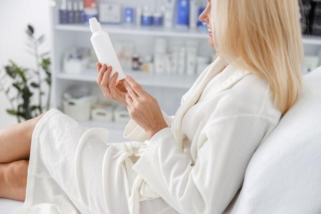 Foto sênior caucasiana feminina sorrindo em roupão branco, segurando o frasco de loção no salão de esteticista.