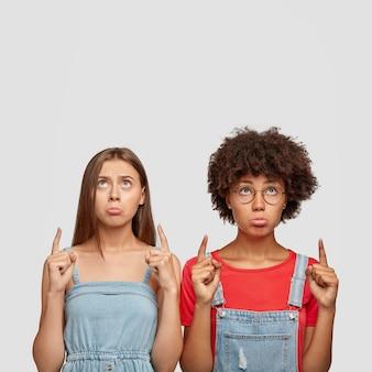 Foto sincera de alunos desanimados com expressões sombrias, lábios baixos