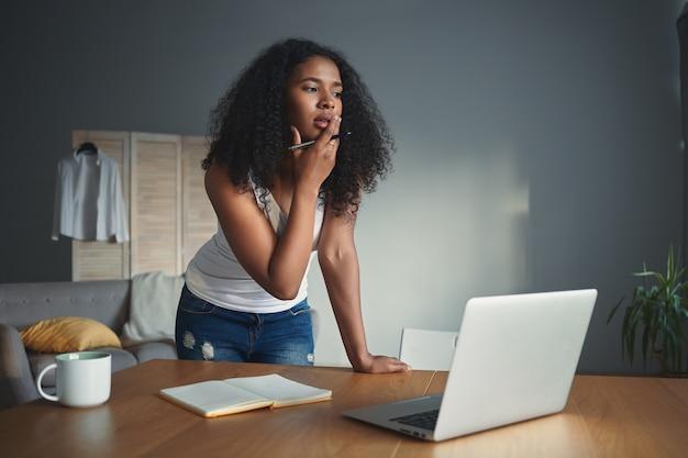 Foto sincera de blogueira pensativa de jovem mestiça posando em ambientes fechados com caneta, em pé no local de trabalho com computador portátil aberto, caneca e caderno na mesa de madeira, com olhar pensativo