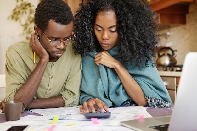 Foto sincera de casal africano estressado revisando suas finanças em casa