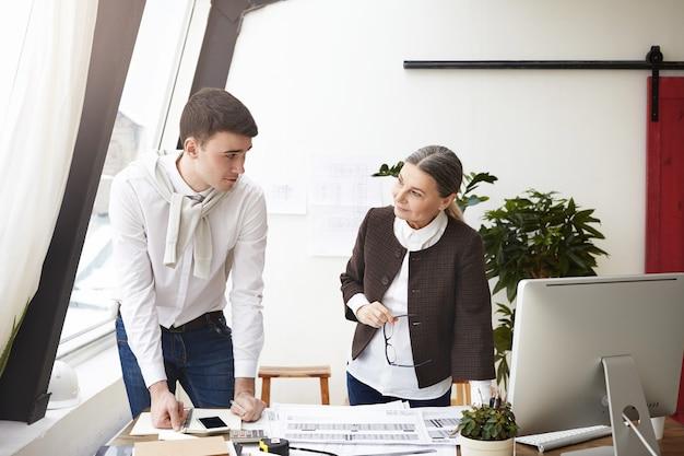 Foto sincera de dois arquitetos europeus discutindo no escritório, em pé na mesa com computador, desenhos e ferramentas, sorrindo um para o outro, satisfeitos com o trabalho comum. pessoas e cooperação