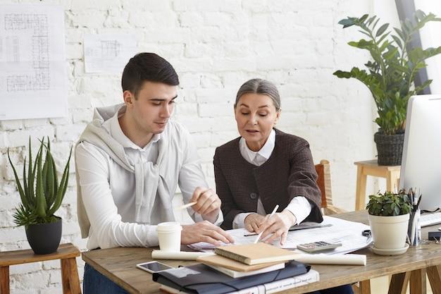 Foto sincera de dois colegas de trabalho fazendo um brainstorming no escritório: engenheira-chefe de meia-idade provando seu ponto de vista para seu jovem colega moreno, apontando para a planta na frente dela na mesa