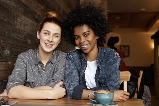Foto sincera de duas lésbicas felizes passando um bom tempo juntas tomando um café em um café aconchegante