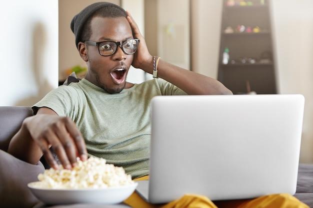 Foto sincera de engraçado jovem de pele escura nos óculos e chapéu assistindo futebol online, usando computador laptop e comendo pipoca, sentado no confortável sofá cinza em casa, tocando o rosto em choque