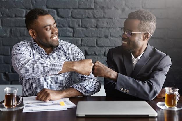 Foto sincera de felizes empresários de pele escura e bem-sucedidos, vestindo roupas formais e batendo os punhos