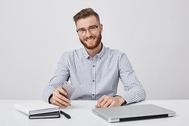 Foto sincera de homem bem sucedido com barba espessa, usa tecnologia moderna para trabalhar