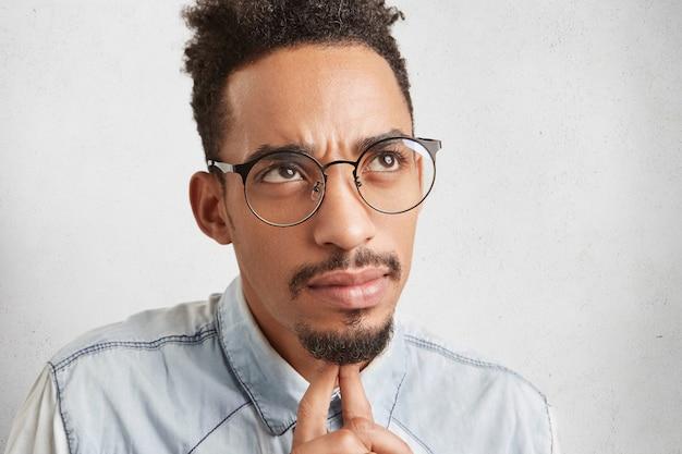 Foto sincera de um homem pensativo com rosto oval, expressão facial séria, olha para cima, mantém os dedos sob o queixo