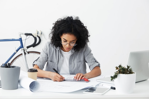 Foto sincera de uma arquiteta afro-americana profissional segurando uma régua e uma caneta