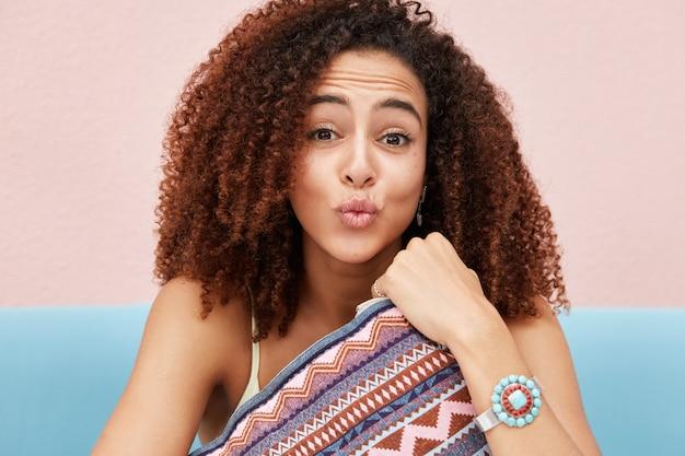 Foto sincera de uma jovem afro-americana engraçada fazendo carranca, lábios arredondados e cabelo crespo e encaracolado