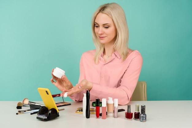 Foto sincera de uma jovem e bonita blogueira caucasiana apresentando produtos de beleza e transmitindo vídeo ao vivo para a rede social, mostrando creme anti-envelhecimento durante a gravação do tutorial de maquiagem diário