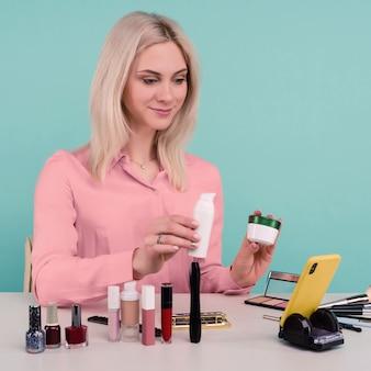 Foto sincera de uma jovem e bonita blogueira caucasiana apresentando produtos de beleza e transmitindo vídeo ao vivo para a rede social, mostrando creme anti-envelhecimento enquanto grava o tutorial de maquiagem diário