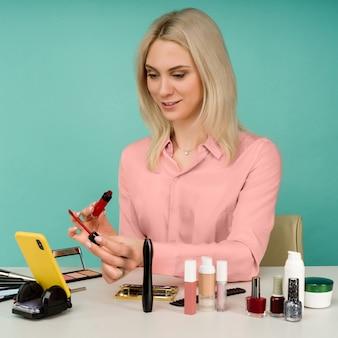 Foto sincera de uma jovem e bonita blogueira caucasiana apresentando produtos de beleza e transmitindo vídeo ao vivo para a rede social, usando brilho labial enquanto grava o tutorial de maquiagem diário