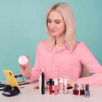 Foto sincera de uma jovem e bonita blogueira caucasiana apresentando produtos de beleza e transmitindo vídeo ao vivo para a rede social