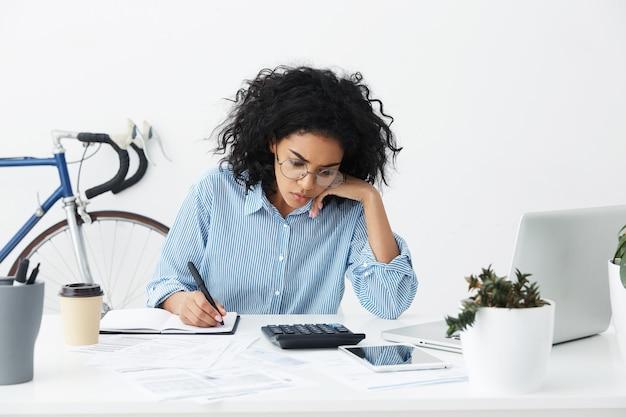 Foto sincera de uma jovem empresária confiante e trabalhadora com cabelo encaracolado