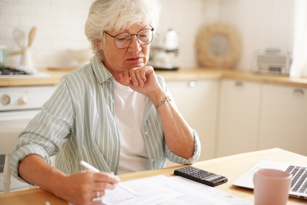 Foto sincera de uma mulher caucasiana aposentada séria usando óculos, calculando despesas, tentando economizar dinheiro para uma compra cara, pagando contas domésticas online usando um dispositivo eletrônico na mesa da cozinha