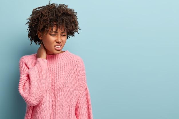 Foto sincera de uma mulher negra desesperada e infeliz que sofre de dores no pescoço, com excesso de trabalho
