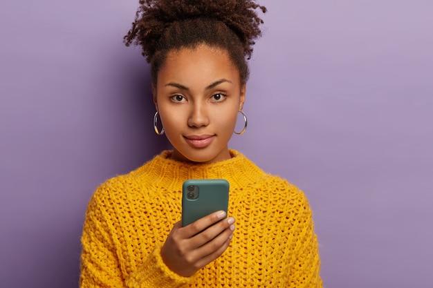 Foto sincera de uma mulher séria da geração y com cabelos escuros encaracolados, usa o celular, olha diretamente para a câmera e usa roupas amarelas
