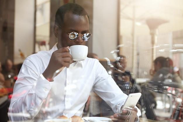 Foto sincera do bem sucedido empresário preto elegante em óculos de sol redondos, tendo cappuccino de manhã na cafeteria, usando telefone celular