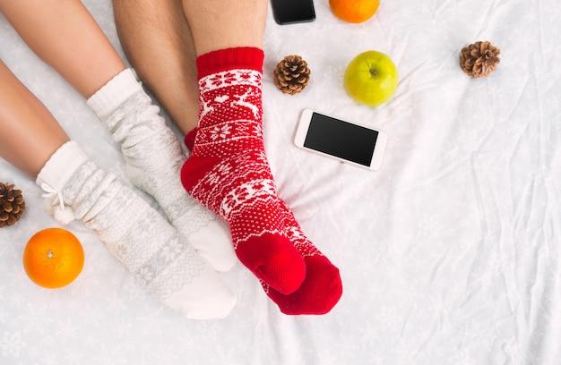 Foto suave de mulher e homem na cama com telefone e frutas, ponto de vista superior. pernas femininas e masculinas de casal em meias de lã quentes.