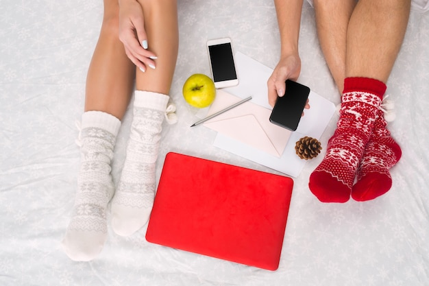 Foto suave de mulher e homem na cama com telefone, laptop e frutas, ponto de vista superior. pernas femininas e masculinas de casal em meias de lã quentes. natal, amor, conceito de estilo de vida
