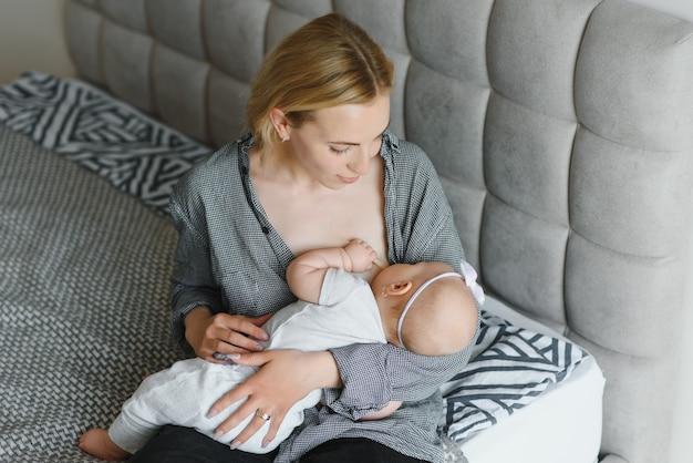 Foto suave jovem mãe amamentando seu bebê em casa em quarto branco