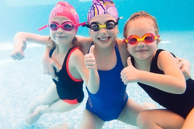 Foto subaquática de jovens amigos na piscina.