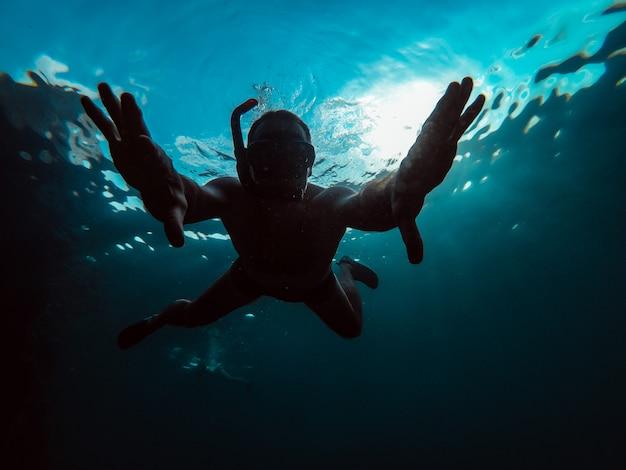 Foto subaquática do homem mergulhar no mar