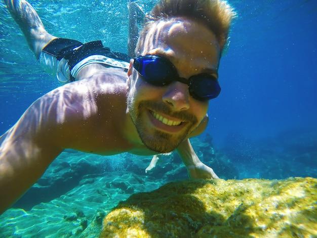 Foto subaquática perto de um jovem turista feliz e sorridente nadando no mar turquesa sob a superfície perto de recifes de coral para as férias de verão.