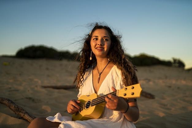 Foto superficial de uma mulher sorridente tocando um ukulele amarelo na praia